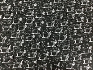 Black fabric covered with white sewing machines.