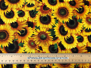 Ruler on fabric that is covered with sunflowers, leaves and ladybugs.