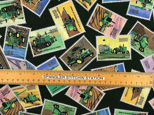 Ruler on green cotton fabric covered with John Deer Stamps.