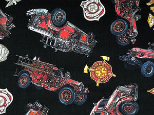 Close up of black cotton fabric covered with firetrucks and shields.