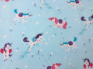 Light blue cotton fabric covered with unicorns.