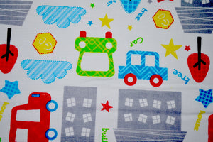 Close up of cars and trucks on white cotton fabric.