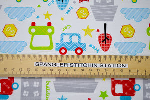 Ruler on white cotton fabric to show sizing of cars.