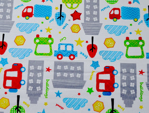 White cotton fabric covered with cars, trucks, trees, clouds, buildings and more.