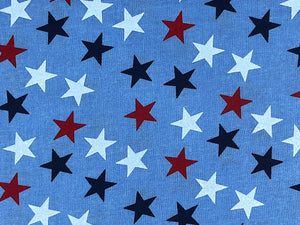 Close up of wide blue cotton fabric that is covered in red, white and blue stars.