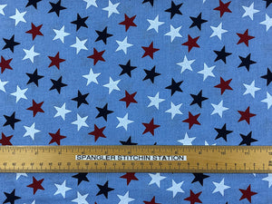 Ruler on wide blue cotton fabric that is covered with red, white and blue stars.