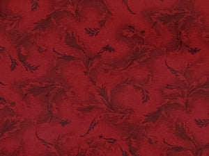 Close up of red cotton fabric covered with leaves.