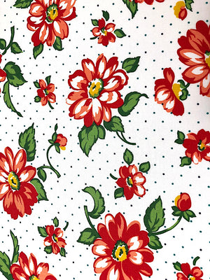 White cotton fabric covered with red flowers and green leaves.