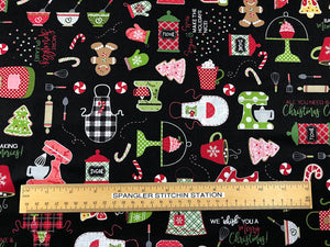 Ruler on black fabric that is covered with kitchen blenders, aprons, cookies, whisks, candy and more.
