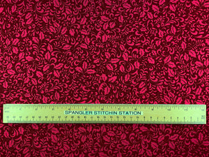 Ruler on red holly leaf fabric.