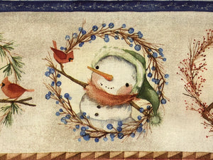 Close up of a snowman looking at a red bird on cotton fabric.