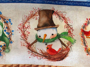 Close up of a snowman looking at a red bird in a nest on cotton fabric