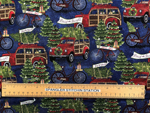 Ruler on blue cotton fabric that is covered with red trucks and bicycles hauling trees.