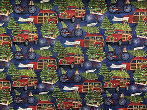 Blue cotton fabric covered with red trucks and bicycles hauling trees