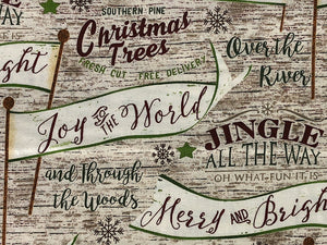 Close up of cotton fabric covered with Christmas sayings such as Jingle all the Way and Over the River.