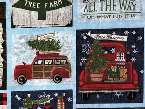 Close up of cotton fabric covered with Christmas trees, red trucks and Christmas sayings