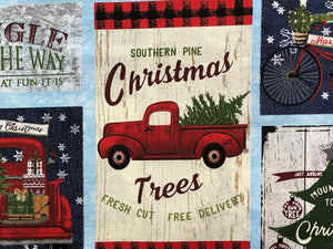 Close up of cotton fabric covered with red trucks, Christmas trees and sayings.