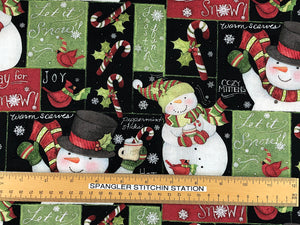 Ruler on black cotton fabric covered with snowmen.