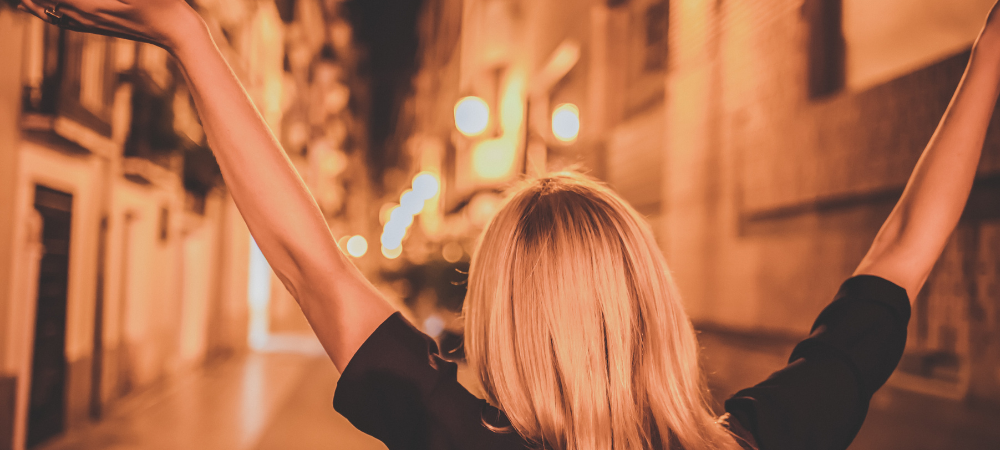 A woman with her arms raised walking down a city street