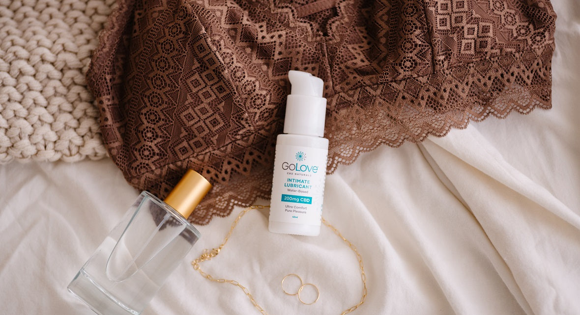 A bottle of GoLove CBD Lube laying on a brown bra top