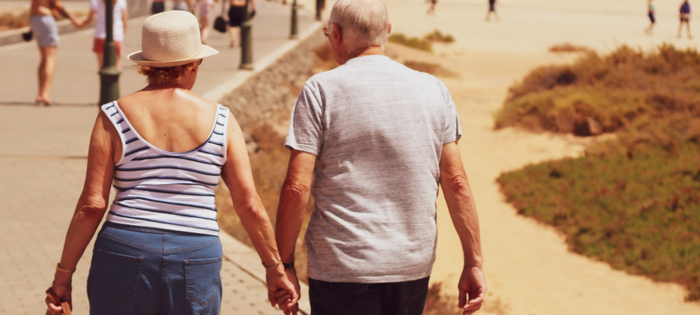An older couple walking by beach holding hands