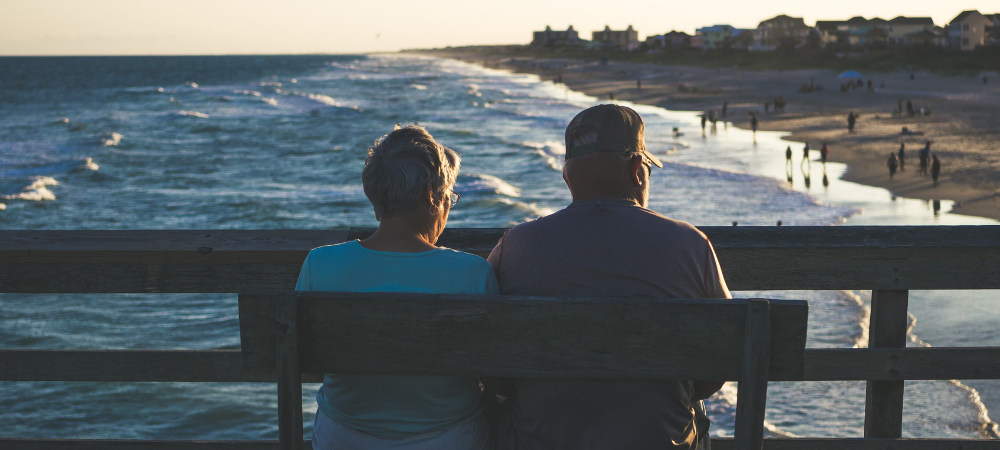 An older couple sitting on a bench looking at the ocean