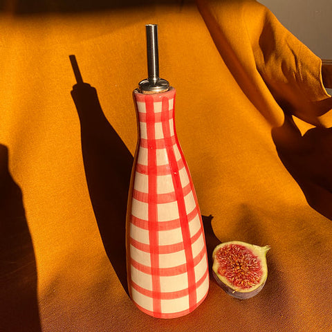 A hand painted olive oil tall bottle in red gingham print