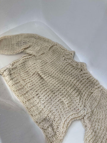 Chunky knit jumper submerged in water in bath