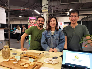 The three founders of Neophyto pose at a food fair with Neocheese displayed.