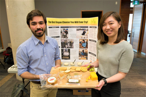 Two founders of Neophyto holding out a display of Neocheese.