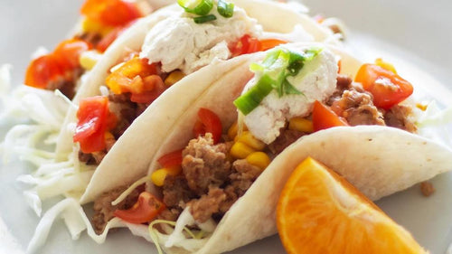 Three tacos made with Neokit™ and garnished with vegetables.