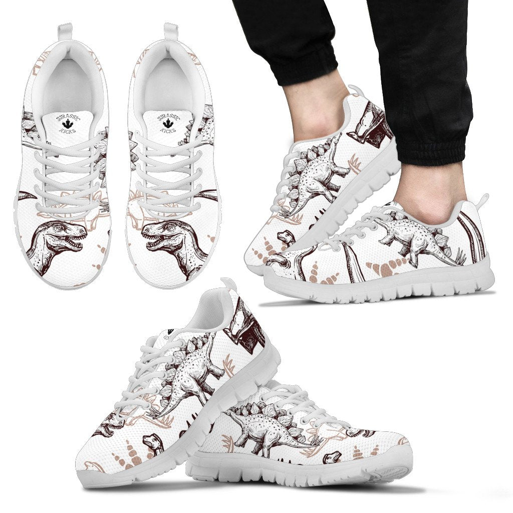Kid wearing a pair of dinosaur shoes with brown stenciled dinosaurs on a white base. Featuring T-Rex and Stegosaurus.