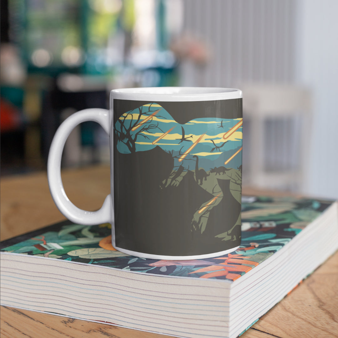A dinosaur mug sitting on a book about dinosaurs. The mug features a dark grey background, with a stencil of a T-Rex. Inside the stencil of the T-Rex shows the final event of the dinosaurs with meteors raining down.