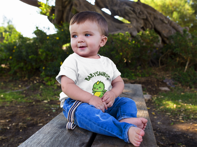 A baby wearing a t-shirt with a cute baby dinosaur titled Babysaurus. Perfect baby shower gift.
