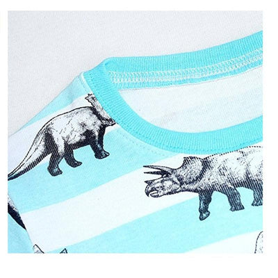 Up close view of dinosaurs printed on a light blue and white kids dinosaur pajamas.