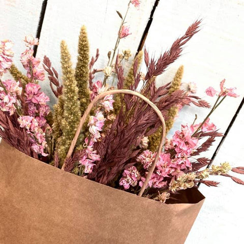 pink and blush dried flowers in a brown kraft bag