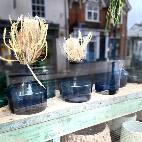 dried flowers in blue vases in a table in a shop window