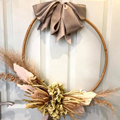 wreath adorned with dried protea flowers and ribbon
