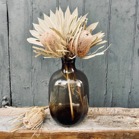 dried protea and palm in a glass vase