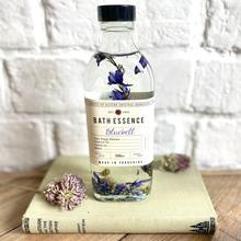 Glass bottle with dried bluebell flowers in bath essence sitting on a book