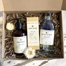 a giftbox with a glass bottle of bluebell essence, a bluebell hand cream and a bluebell hand soap in pump dispenser in a pretty box