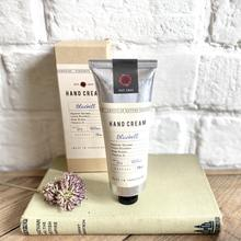 Tube of natural bluebell hand cream standing on a book with dried flowers on display