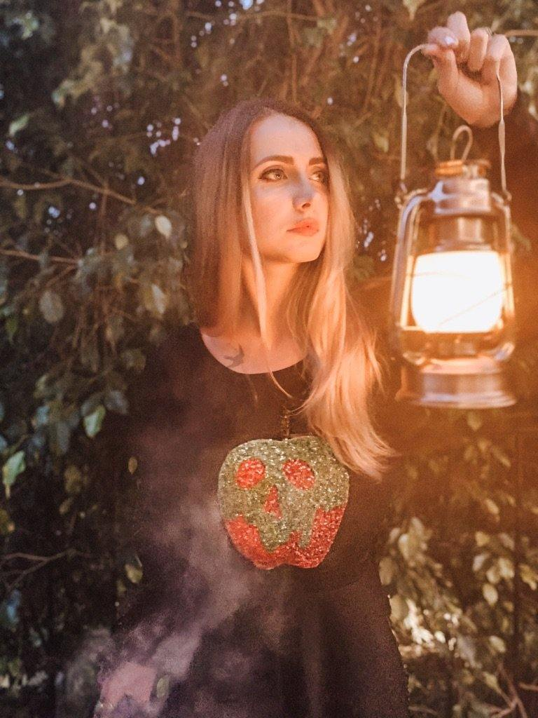 Model wearing green and red poison apple sequin sweatshirt