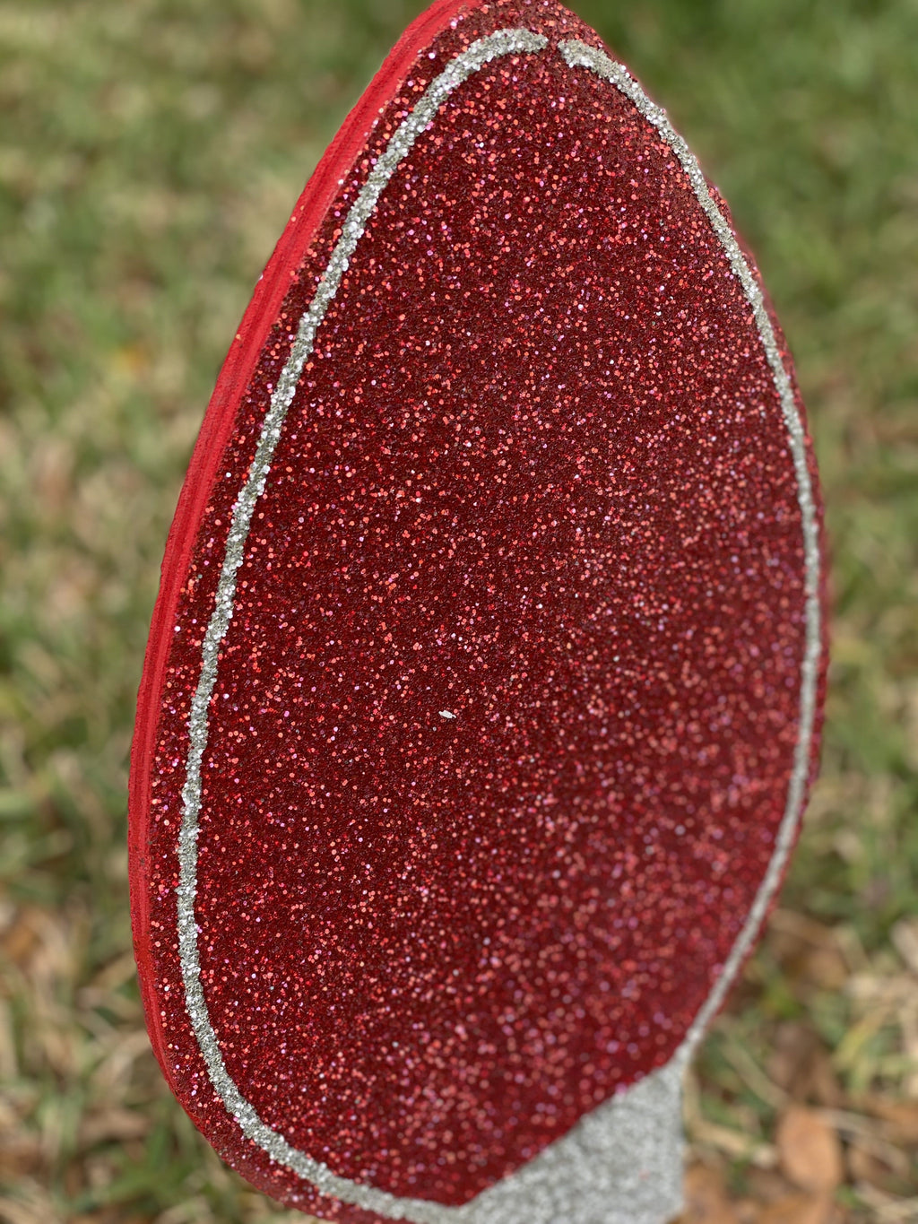 side view of red glitter painted yard art design