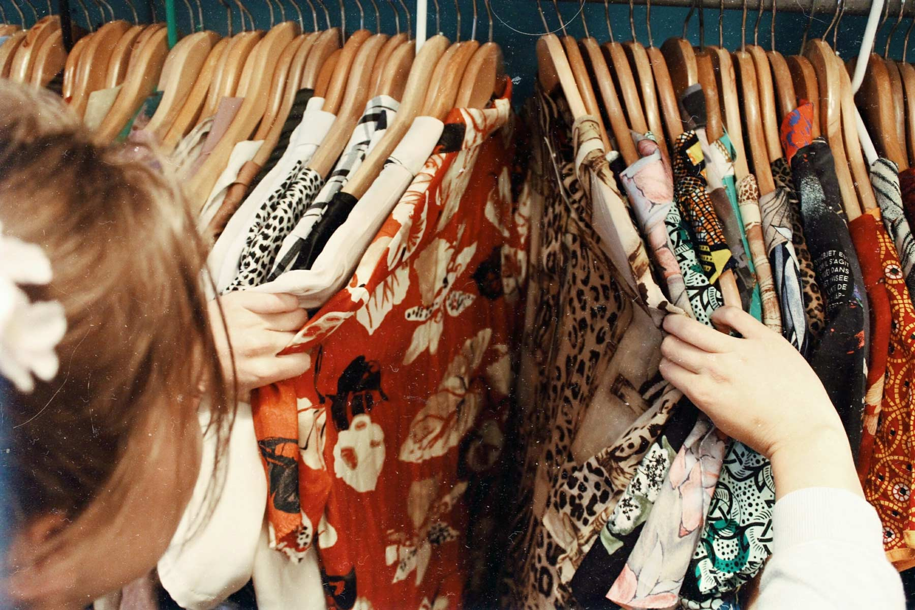 girl looking through clothing rails