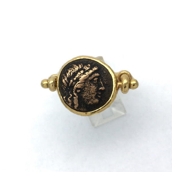 Sturup ring featuring an ancient bronze Greek coin with the head of Apollo, set in a way that allows the coin to rotate so that coin can be worn with either side showing