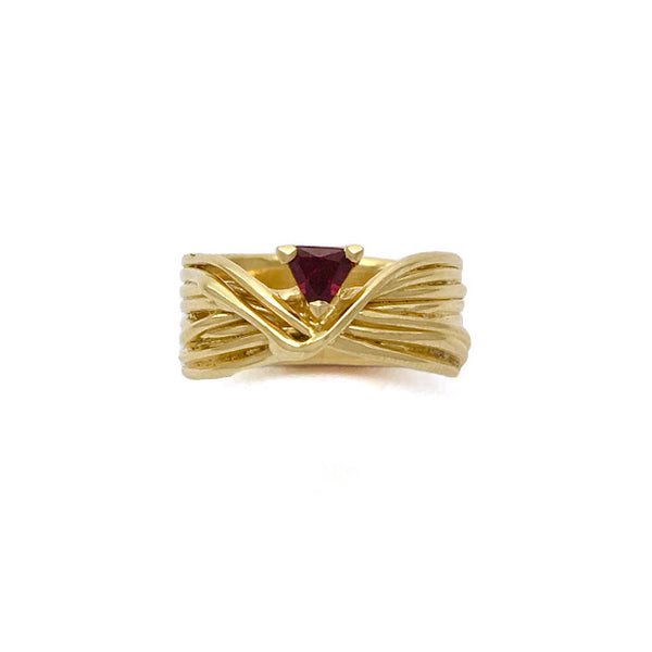 Criss crossed golden cords set with a deep red garnet