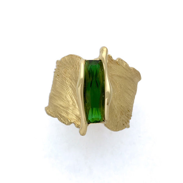 Bright green scissor cut tourmaline set into a feather texture ring
