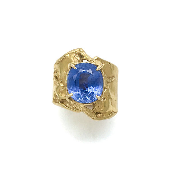 Fluid band rising up to support an oval blue sapphire