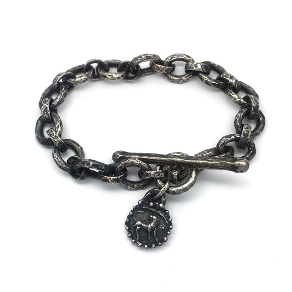 Bracelet composed of heavily textured oval links with a single dangling charm featuring a lion image from an impression of an ancient Roman stone seal